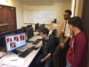 three students looking at their research