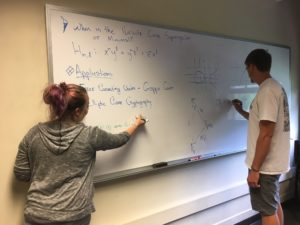 Undergraduates Amethyst Price and Eric Work writing equations on a white board