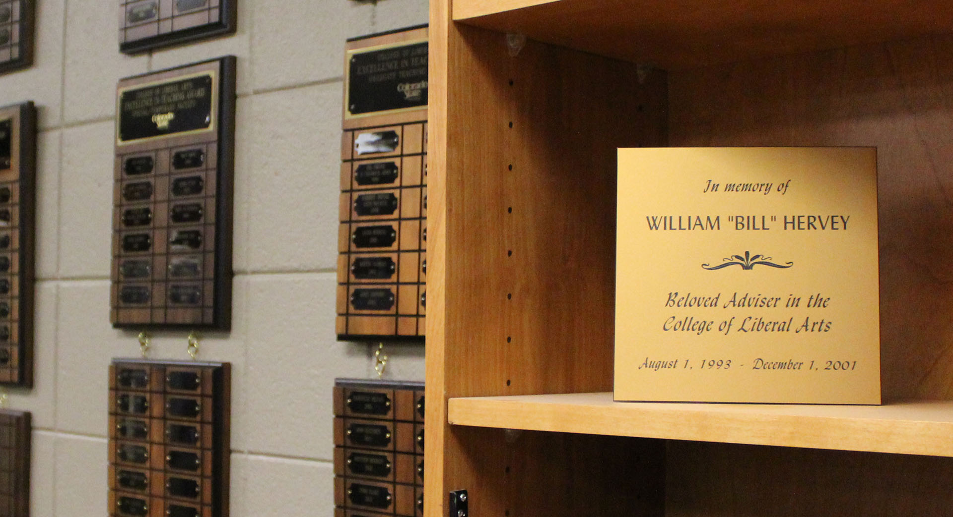 "A memorial plaque sitting on a bookshelf reads ""In memory of Bill Hervey beloved adviser in the College of Liberal Arts."""