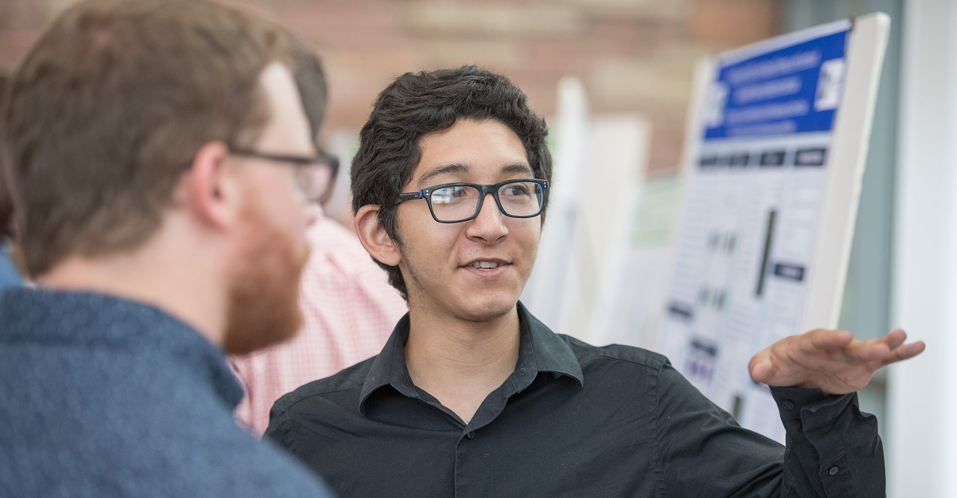 student speaks at research poster session