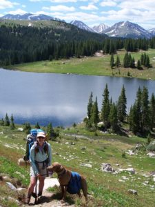Mary Young and dog backpacking in the mountains