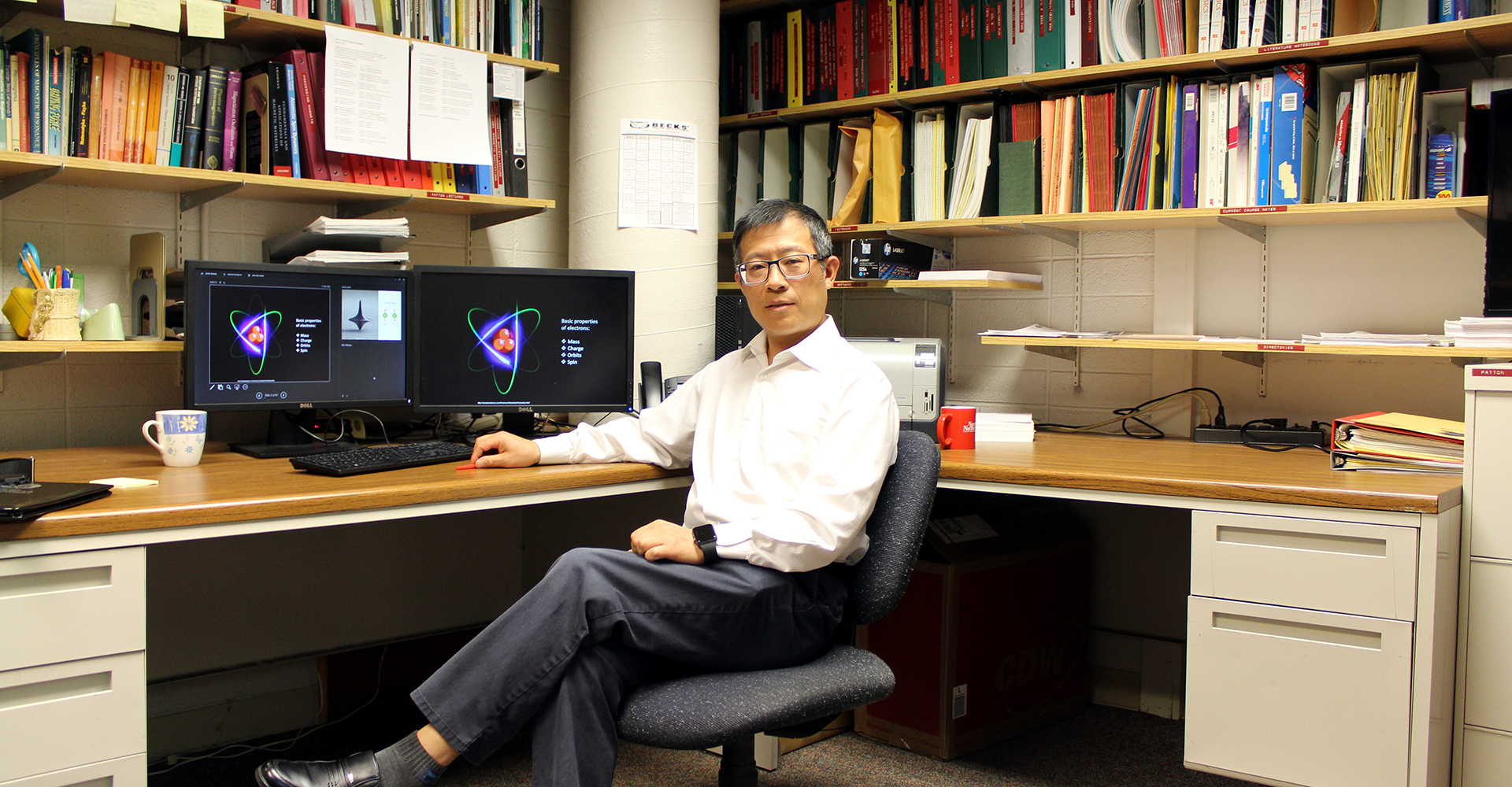 Dr. Mingzhong Wu sits at his desk in the Physics building.