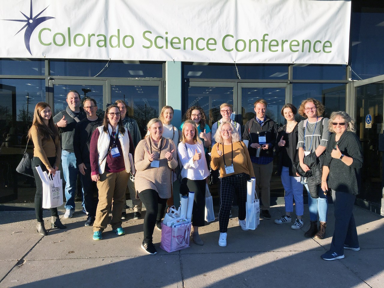 A group of natural sciences students stands in front of ta sign reading Colorado Science Conference.