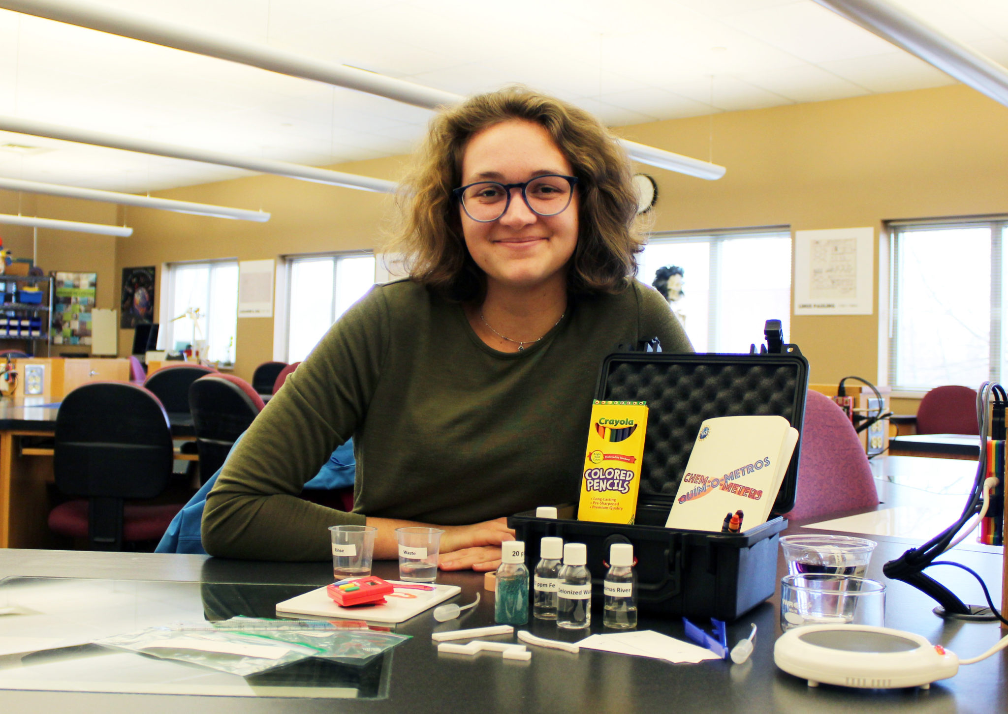 Student Chloe Beardsley sits in a science lab with the Chem-O-Meter kit on the table in front of her.